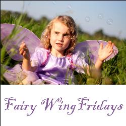 Girl in fairy wings blowing bubbles
