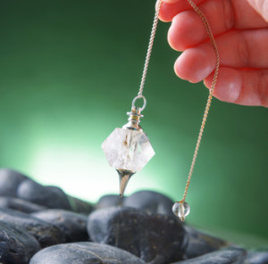 Hand with pendulum for dowsing.