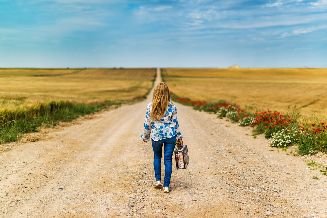 woman with a suitcase walking down a dirt road between fields of dried crops